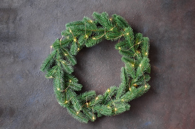 Christmas door wreath made of tree fir branches with lights