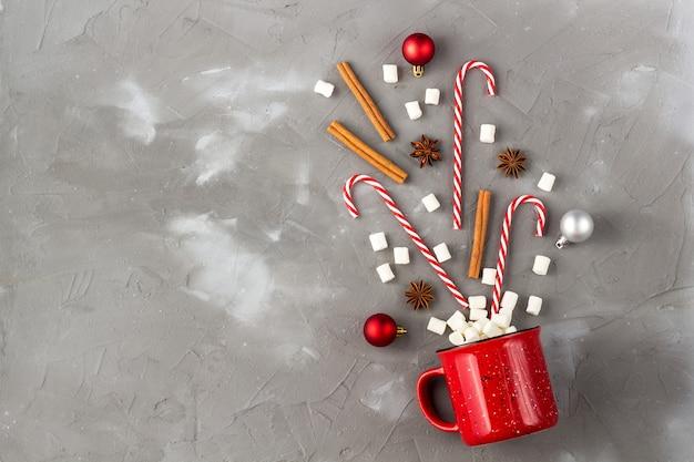 크리스마스 음료 축 하 개념입니다. 회색 테이블에 마시멜로 아니스 계피와 사탕 지팡이가 있는 컵