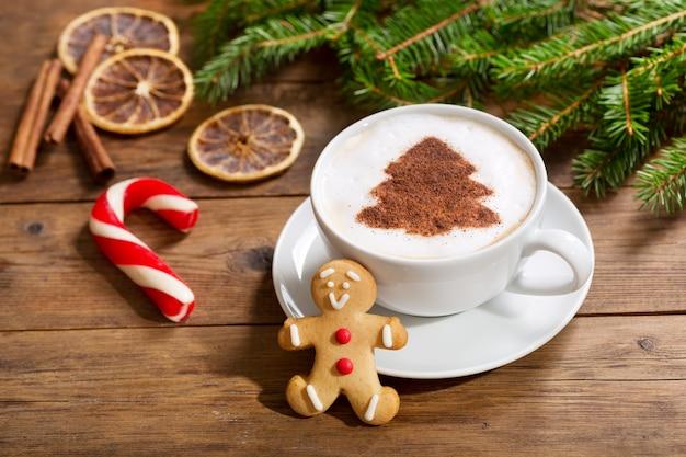 Рождественский напиток чашка кофе капучино с рисунком елки и имбирным печеньем