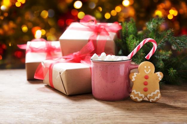 Рождественский напиток чашка горячего шоколада с зефирным имбирным печеньем и рождественскими подарками