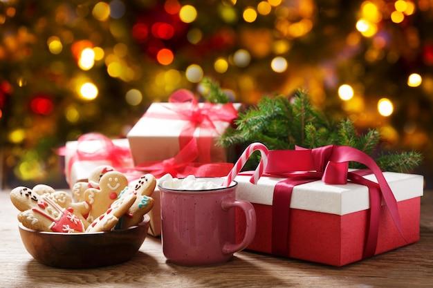 Рождественский напиток чашка горячего шоколада с зефиром, пряники и рождественские подарки