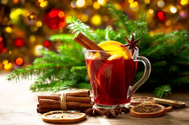 Рождественский напиток. стакан горячего глинтвейна с апельсинами, анисом и корицей на праздничном фоне
