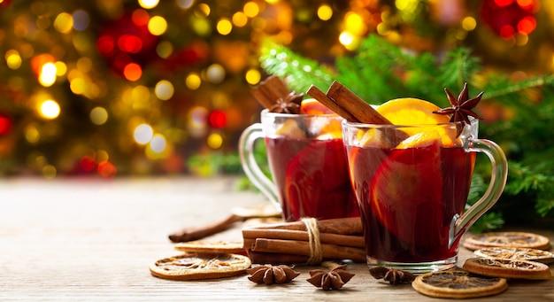 Рождественский напиток. бокалы горячего глинтвейна с апельсинами, анисом и корицей на праздничном фоне