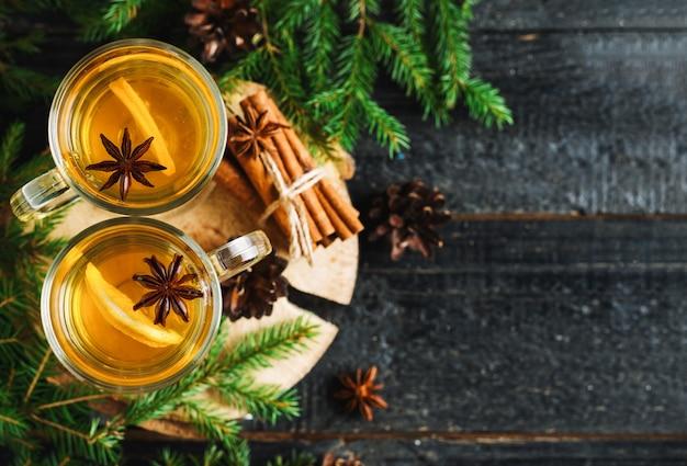 クリスマスドリンクグロッグレモン、シナモン、スプルースの枝とコピースペースを持つ木製テーブルの上のワイン