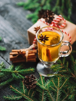 Christmas drink grog with lemon, cinnamon, wine on wooden table with gift boxes for holiday