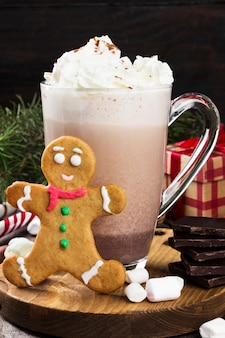 Christmas drink hot chocolate with cream, marshmallows and gingerbread on a wooden surface