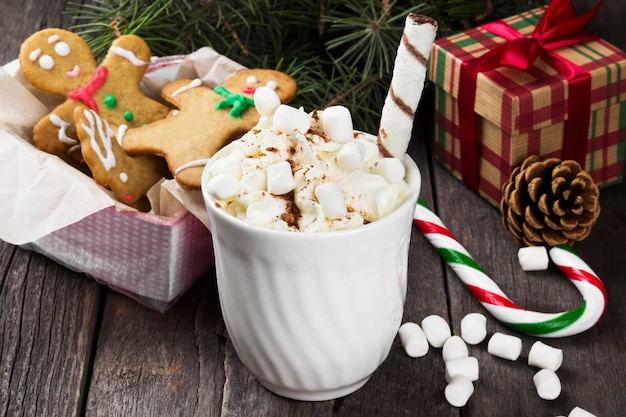 Christmas drink hot chocolate with cream and marshmallows on wood