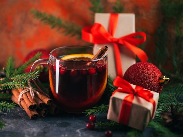 Рождественский напиток глинтвейн в стеклянной чашке на столе с ветками ели