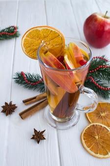 クリスマスドリンク。白い木製の背景にリンゴ、オレンジ、クランベリー、スパイスとホットワイン。場所は垂直です。閉じる。