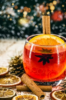 Рождественский напиток сангрия или глинтвейн, или брей, с яблоками, апельсинами, гранатом и палочками корицы.