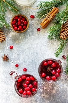 Christmas drinks hot winter drink with cranberries and cinnamon on a light stone table top view