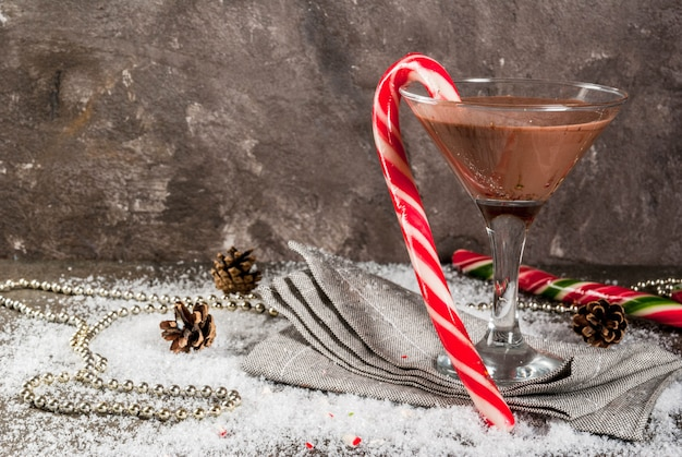 Christmas drinks, peppermint mocha martini cocktail with candy cane, on grey   copyspace