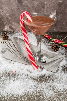 Christmas drinks, peppermint mocha martini cocktail with candy cane, on grey