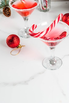 Christmas drinks, pink peppermint martini cocktail with xmas decoration and candy cane sweet on white marble kitchen table, copyspace