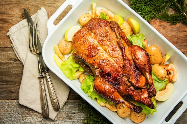 Christmas duck with apples and herbs in white pan over wooden background, top view