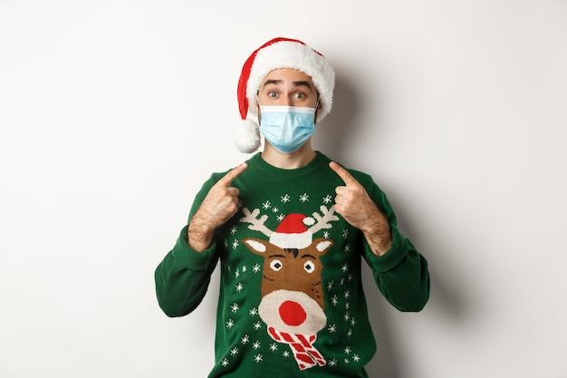 전염병 동안 크리스마스, covid-19 개념. 산타 모자를 쓴 남자가 얼굴 마스크를 가리키며 새해와 사회적 거리, 흰색 배경을 축하합니다.