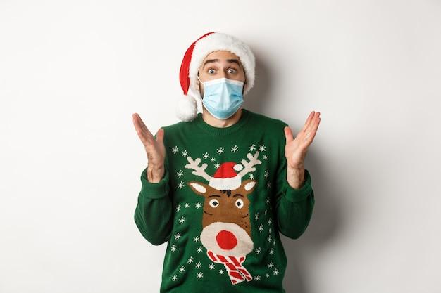 전염병 동안 크리스마스, covid-19 개념. 의료용 마스크, 산타 모자, 스웨터를 입은 놀란 남자가 새해 파티를 축하하고 흰색 배경 위에 서 있습니다.