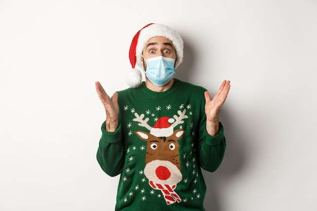 Christmas during pandemic, covid-19 concept. surprised guy in medical mask, santa hat and sweater celebrating new year party, standing over white background.