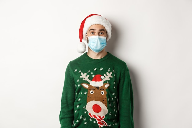 Natale durante la pandemia, concetto di covid-19. giovane uomo con cappello da babbo natale e maschera facciale che celebra la festa di capodanno con misure preventive, sfondo bianco.
