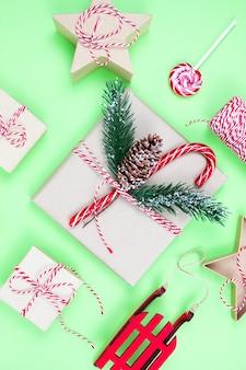 緑のクリスマスの環境にやさしいパッケージギフト、エコクリスマスホリデーコンセプト、エコ装飾お祝い冬の表面。キャンディーとモミの木、紙箱、木のおもちゃをプレゼント