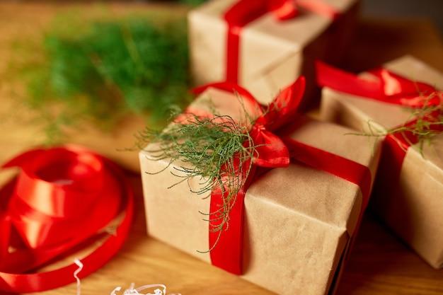 クリスマスの環境にやさしい包装クラフト紙とモミの枝のホリデーシーズンのギフト、木製のテーブルの上のクリスマス、エコの装飾、クリスマスプレゼントギフトボックス