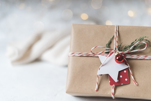 Christmas eco gift with empty tag. glowing snow bokeh, coniferous branch