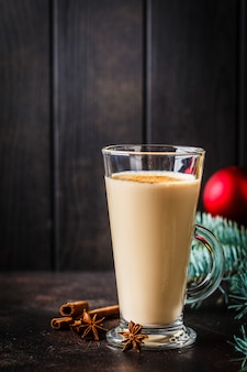 Christmas eggnog in a glass in christmas background, copy space.