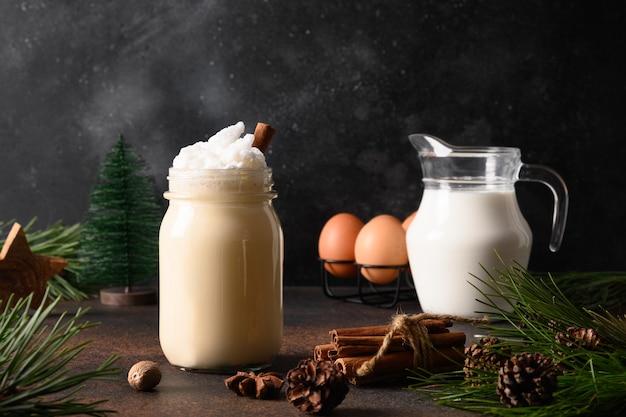 ダークブラウンの背景に材料とメイソンジャーのクリスマスエッグノッグ。閉じる。