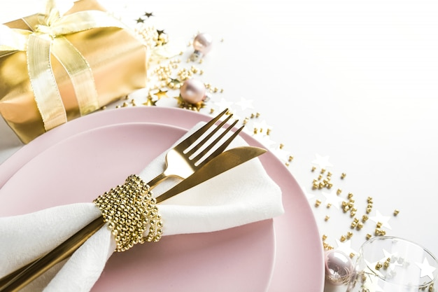 Christmas elegance table setting with pink dishware, golden silverware on white. top view. xmas dinner.