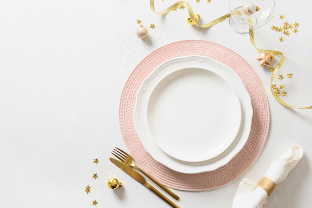 Christmas elegance table setting with pink and golden decorations on white.