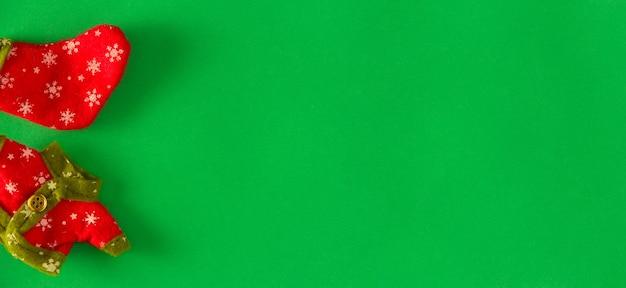 緑の背景にクリスマスのエルフの服とクリスマスの靴下。スペースをコピーします。セレクティブフォーカス。