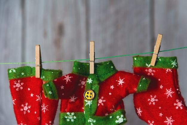 クリスマスエルフの服は洗濯バサミで吊るされました。スペースをコピーします。セレクティブフォーカス。