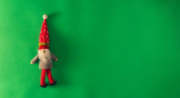 緑の背景にクリスマスエルフ。スペースをコピーします。セレクティブフォーカス。