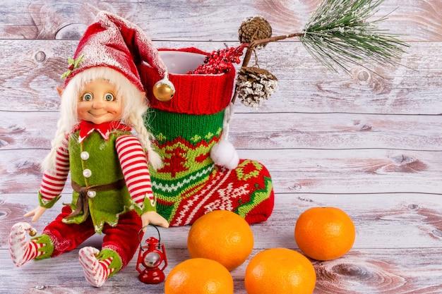Рождественский эльф сидит рядом с рождественский носок на светлом деревянном фоне.