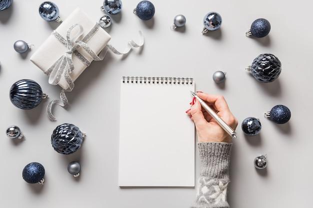 Рождественский пустой бланк для планирования нового года в руках женщины с синими украшениями на сером. вид сверху.