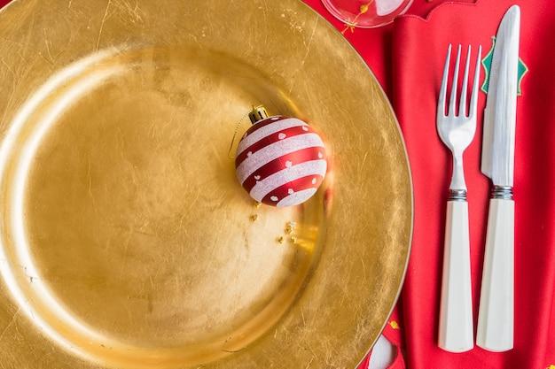 夕食に提供されるクリスマスの空の金色のプレートのクローズアップ