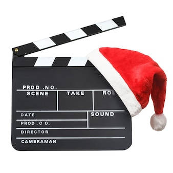 Christmas entertainment concept. santa hat hanging on a movie clapper board isolated on a white background