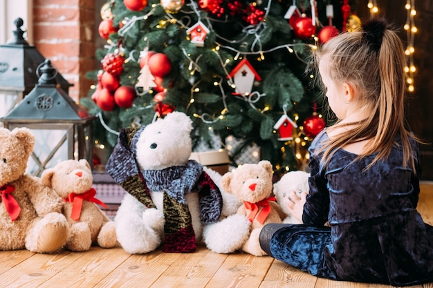 Christmas eve. back view of little girl sitting alone on floor at decorated fir tree, playing with her teddy bears.