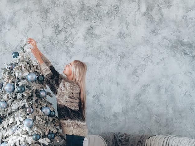 크리스마스 이브. 전나무 나무를 장식하는 스웨터에 금발 아가씨