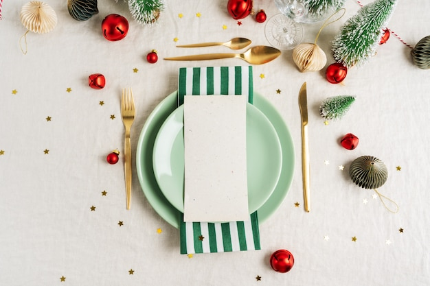 Christmas eve celebration party table setting with plates, golden cutlery over linen tablecloth background
