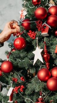 크리스마스 이브 개념. 빨간 공, 딸기, 흰색 별 장신구와 녹색 전나무 나무를 장식하는 남자의 자른 샷.