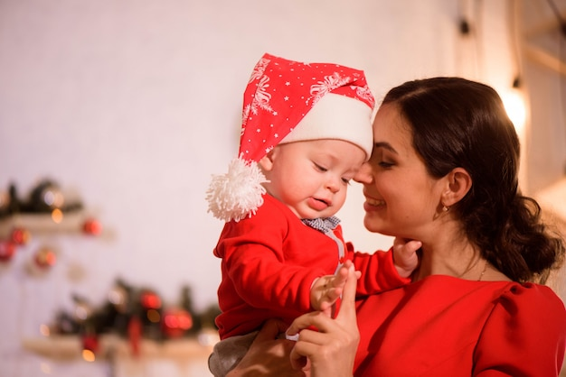 Christmas eve. family mother and baby in santa hatplay game at home near the fireplace.