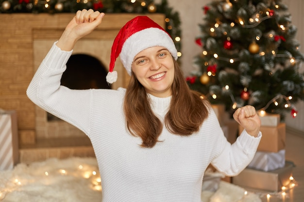 Christmas eve. happy woman with hands up dancing merrily with toothy smile, lady wearing sweater and red santa hat, posing in living room decorated with garland and x-mas tree.