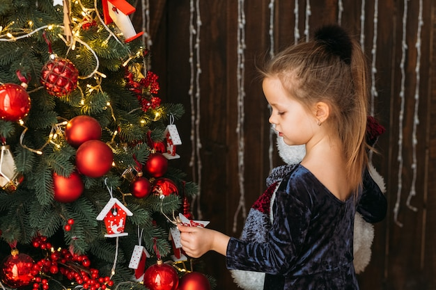 Christmas eve. side view of cute little girl standing at decorated fir tree, waiting for santa with gifts.
