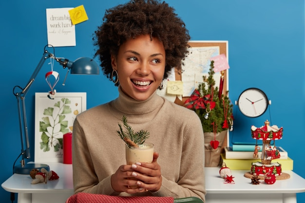 Christmas eve, traditional drink and holiday preparation. cheerful woman with afro hairstyle holds glass of eggnog cocktail, looks with broad smile