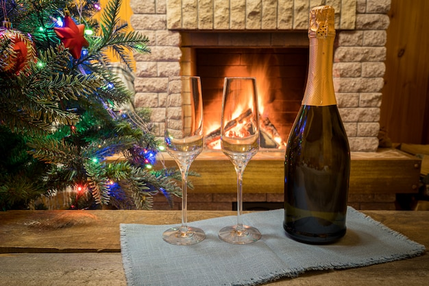 Christmas eve. two glasses of champagne wine near cozy fireplace and before christmas tree decorated toys and christmas lights in country house.