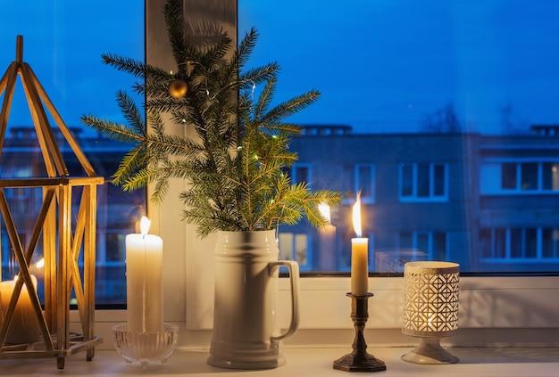 燃えるろうそくとクリスマスイブニング窓辺