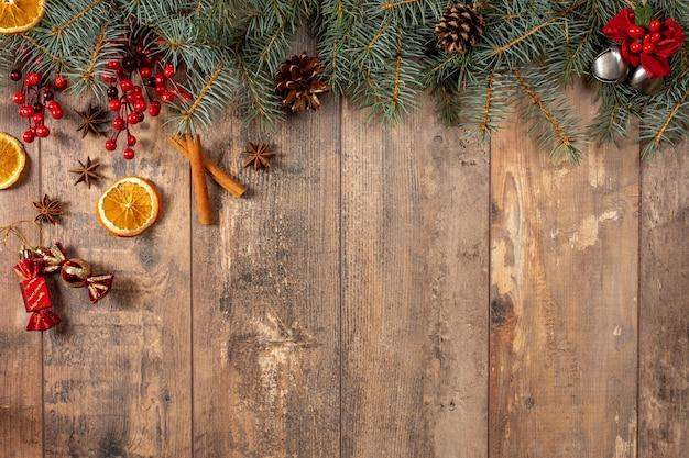 素朴な木の水平方向の背景上のクリスマス常緑樹の枝とベリー。