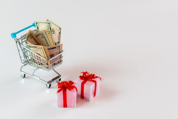 Christmas expense planning concept , gift boxes and shopping cart full of money, isolated on white