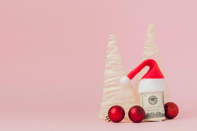 Рождественские расходы. розовый кожаный кошелек с колпаком деда мороза, подарком, елкой и банкнотами долларов.